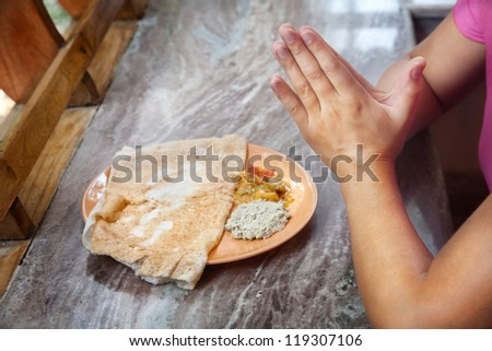 Woman praying in front of masala dosa Indian traditional vegetarian dish with coconut chutney in India