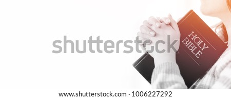 woman praying on holy bible in the morning.teenager woman hand with Bible praying,Hands folded in prayer on a Holy Bible in church concept for faith, spirituality,worship and religion.