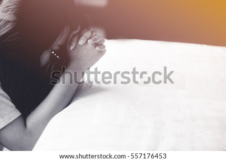 woman praying on the bed in the morning.teenager woman hand with Bible praying,Hands folded in prayer on the bed in the morning concept for faith, spirituality and religion.black and white tone.