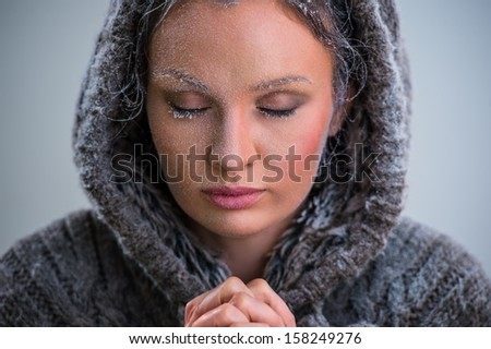 Woman praying. Wearing hoodie. Frost on her face #158249276