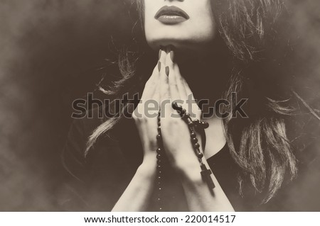 woman praying with rosary sepia ...