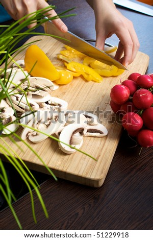 Woman prepares mushrooms, pepper and radish for a salad on a wooden cutting board