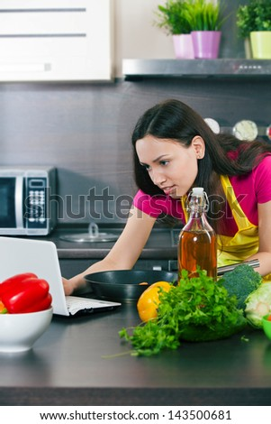 Woman prepares the food in the kitchen and looks into the computer