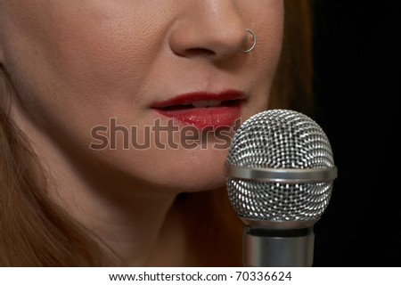 Woman prepares to sing live - closeup of microphone and mouth