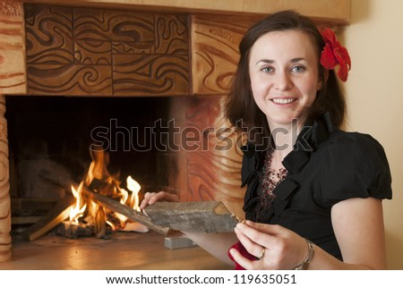 woman prepares wood for fireplace in room - stock photo