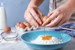Woman preparing batter for thin pancakes at light grey table, closeup