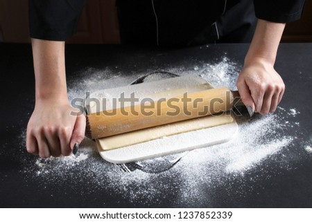 Woman preparing buns from puff pastryat table in bakery. The cook preparing buns at table in bakery. Cooking Process Of Apple Roses. Step four prepare the dough for baking. Cooking Process Concept