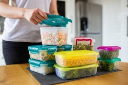 Woman preparing containers with frozen mixed vegetables for refrigerator.