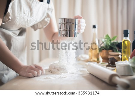 Woman preparing dough basis.Ingredients for baking.Female hands spilling powder on dough.Making dough by female hands.Cooking and baking concept
