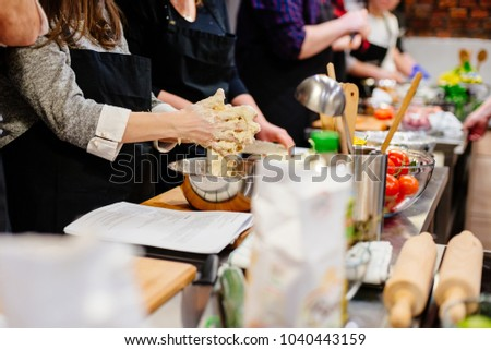 Woman preparing dough in the bowl. Culinary workshops #1040443159