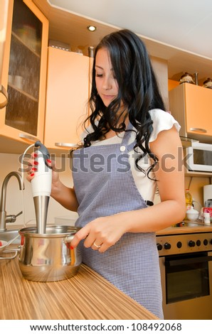 Woman preparing food with a handblender in her kitchen