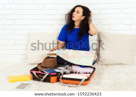 Woman preparing for the journey. Young girl are packing suitcases for the trip. Trip planning concept. People, travel and lifestyle concept. Woman explores the map while sitting on the floor