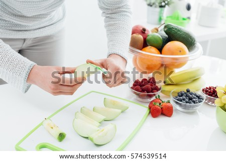 Woman preparing fruit in her kitchen, she is slicing and peeling apples on a chopping board