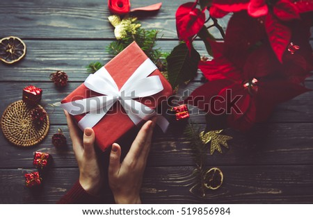Woman preparing gift box for present on table with Poinsettia. Evening before Christmas