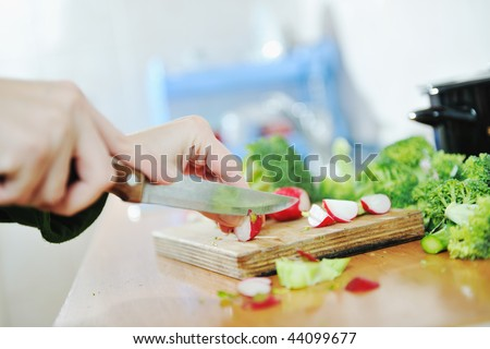 woman preparing healthy food salad with green and red vegetable and knife