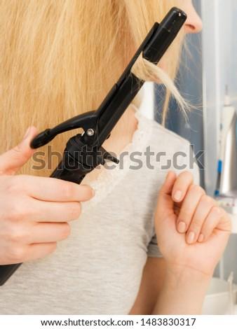 Woman preparing her blonde hair, using curling pin in home bathroom. Hairdo curler creating hairstyle.