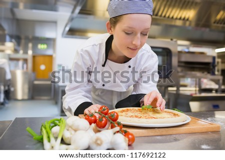 Woman preparing pizza in kitchen