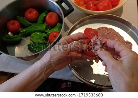Woman preparing stuffed ground beef tomatoes and peppers Stok fotoğraf ©