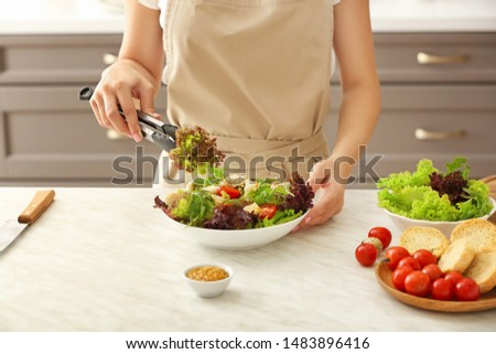 Woman preparing tasty salad in kitchen #1483896416