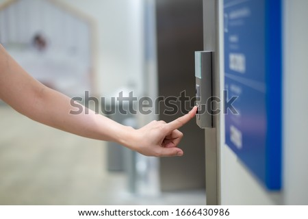 Woman press on elevator control panel in the building to call the elevator. Woman using elevator to reach higher floor in high building.