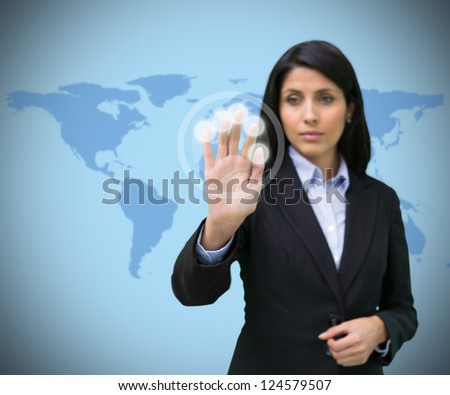 Woman pressing hand to holographic screen against world map