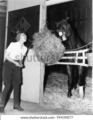 Woman pretending to eat hay bale with horse
