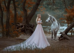 Woman princess met unicorn horse with Horn. Fairy forest autumn tree. lake river fog. blonde girl angelic face elegant hairstyle medieval white clothing long vintage dress skirt train. Artistic Photo