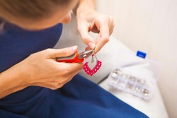 woman process hand made design freelance work at home make accessories red earrings weave knot products from thread rope beads and metal. creation close up repair in detail
