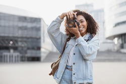 Woman professional photographer with dslr camera outdoors portrait.  Mixed race girl in the city taking pictures. Home hobby, lifestyle, travel, people concept