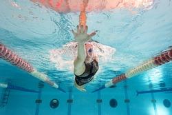 Woman professional swimmer wearing black swimsuit inside swimming pool.