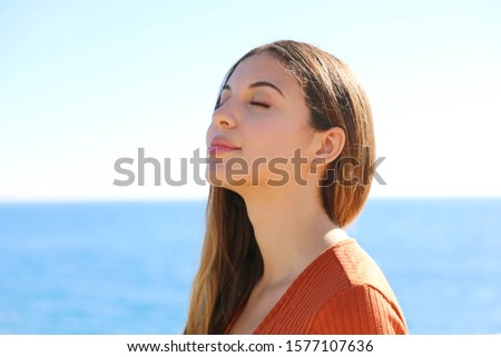 Woman profile portrait breathing deep fresh air on the beach with the ocean on background.