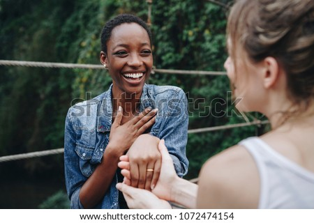 Woman proposing to her happy girlfriend outdoors
