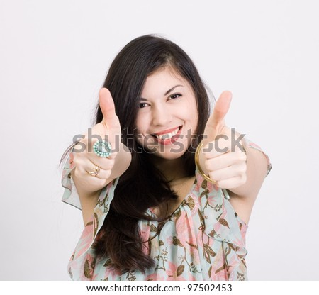 Woman puckering mouth while giving two thumbs up