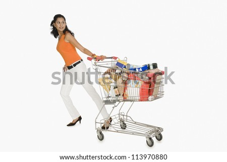 Woman pulling a shopping cart and smiling