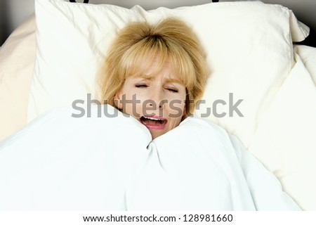 Woman pulling blanket to her face in bed with expression of fear