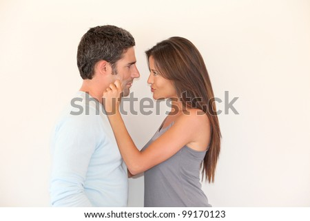 Woman pulling on boyfriend's cheeks - stock photo
