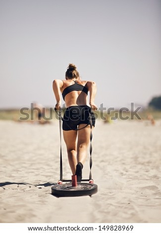 Woman pulling sled during a beach workout