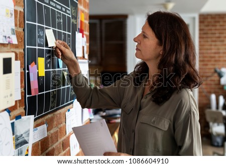 Woman pulling sticky note