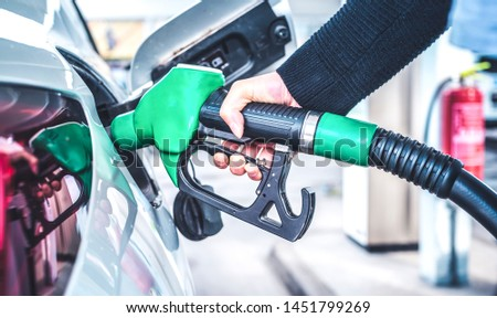 Woman pumping gasoline fuel in car at gas station.
