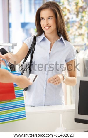 Woman purchasing clothes in shop, getting back credit card, smiling at shop assistant.?