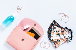 Woman purse with fashionable face masks, hand sanitizer, smartphone and cosmetics on white table top, new normal concept. Stylish protective masks and fashion accessories, copy space