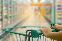 Woman push shopping cart in supermarket. (lens blur effect and vintage color tone)