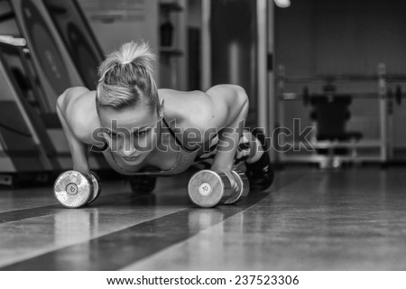Woman push-ups on the floor.Gym woman push-up strength pushup exercise with dumbbell in a fitness workout. Athletic young woman doing exercises on the floor is pushed.
