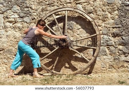 Woman pushed wheel - brickwall background