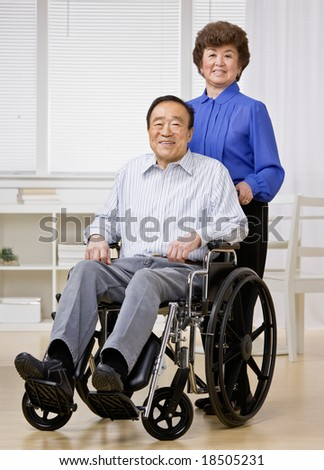 Woman pushing disabled man in wheel chair
