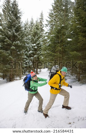 Woman pushing man with backpack up snowy slope in woods