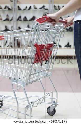 Woman pushing shopping cart in shoe store, close-up