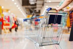 woman pushing shopping cart in shopping mall