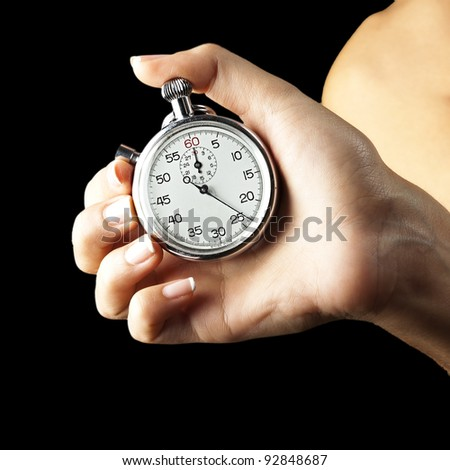 woman pushing stopwatch button against a black background