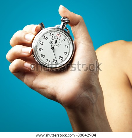 woman pushing stopwatch button against a blue background